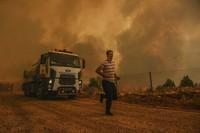 A man runs, in the fire-devastating Sirtkoy village, near Manavgat, Antalya, Turkey, on Aug. 1, 2021. (AP Photo)