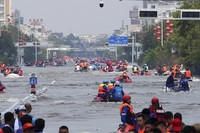 Rescuers use boats to evacuate people from a flooded area in Weihui in central China's Henan Province, on July 26, 2021. (Chinatopix via AP)