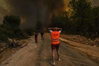 People run away from the fire-devastated Sirtkoy village in Antalya, Turkey, on Aug. 1, 2021. (AP Photo)