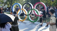 People standing in lines to take a photo with the Olympic Rings outside the Olympic Stadium during the 2020 Summer Olympics, on Aug. 1, 2021, in Tokyo, Japan. (AP Photo/Martin Meissner)