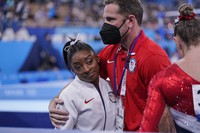 Coach Laurent Landi embraces Simone Biles, after she exited the team final with apparent injury, at the 2020 Summer Olympics, on July 27, 2021, in Tokyo. (AP Photo/Gregory Bull)