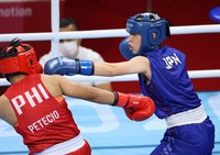 Sena Irie of Japan, right, throws a punch at Nesthy Petecio of the Philippines during the first round of the women's Olympic boxing featherweight final at Tokyo's Ryogoku Kokugikan, on Aug. 3, 2021. (Mainichi/Junichi Sasaki)