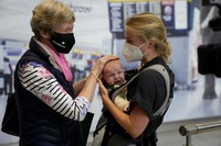 Susan Handfield, left, meets her baby granddaughter Charlotta for the first time, held by her mother Eva as they arrive from a Berlin flight at Terminal 5 of Heathrow Airport in London, Aug. 2, 2021. (AP Photo/Matt Dunham)