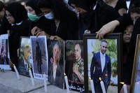 Relatives of victims of the Aug. 4, 2020 Beirut port explosion light candles and hold portraits of their loved ones, in Beirut, Lebanon, on July 4, 2021. (AP Photo/Hassan Ammar)