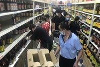Residents rush to stock up on necessities at a supermarket after authorities locked down nearby residential blocks to prevent the spread of the coronavirus in Wuhan in central China's Hubei province, on Aug. 2, 2021. (Chinatopix via AP)