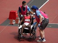 Lucia Moris, of Sout Sudan is assisted from the track after finishing a women's 200-meter first round heat at the Summer Olympics, on Aug. 2, 2021, in Tokyo, Japan. (AP Photo/Charlie Riedel)
