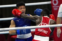 Colombia's Yuberjen Herney Martinez Rivas, right, exchanges punches with Japan's Ryomei Tanaka in their men's flyweight 52-kg quarterfinal boxing match at the Summer Olympics, on Aug. 3, 2021, in Tokyo, Japan. (AP Photo/Themba Hadebe)