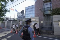 A Japanese police officer stands by media crews in front of the Embassy of Poland in Tokyo where the Belarusian athlete Krystsina Tsimanouskaya who seeks asylum is staying, on Aug. 3, 2021. (AP Photo/Kantaro Komiya)