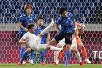 Spain's Javier Puado shot on goal as Japan's Wataru Endo blocks in a men's semifinal soccer match at the 2020 Summer Olympics, on Aug. 3, 2021, in Saitama, Japan. (AP Photo/Martin Mejia)