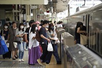 In this July 31, 2021 file photo, passengers wearing face masks board a westbound bullet train at JR Tokyo Station. (AP Photo/Kantaro Komiya, File)