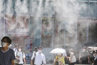 People wearing face masks walk under a cooling water mist during the heat of the day in Tokyo on Thursday, Aug. 5, 2021. (AP Photo/Koji Sasahara)