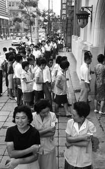 People are seen waiting in front of the Kojimachi public health center in Tokyo to receive vaccines for cholera in this Aug. 27, 1964 file photo. (Mainichi)