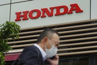 A man wearing a protective mask walks past the logo of Honda Motor Company in Tokyo on May 13, 2021. (AP Photo/Eugene Hoshiko)