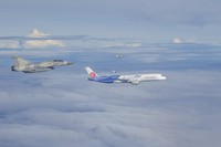 In this photo released by the Military News Agency, Mirage-2000 jet fighters of Taiwan's Air Force fly alongside China Airlines flight CI-101 to honor the return of Taiwan's badminton Olympians as the plane approaches Taoyuan International Airport in Taiwan, on Aug. 4, 2021. (Military News Agency via AP)