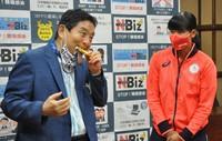 Nagoya Mayor Takashi Kawamura bites the gold medal of Tokyo Games Olympian Miu Goto, a member of the Japan softball team, at the Nagoya city hall in Aichi Prefecture on Aug. 4, 2021. (Mainichi/Masakatsu Oka)