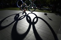 A child sits in the Olympic rings on display outside the Olympic Stadium where the athletic events are underway at the 2020 Summer Olympics, on Aug. 3, 2021, in Tokyo. (AP Photo/David Goldman)