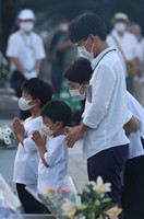 People pray in front of the Cenotaph for the A-bomb Victims at Hiroshima Peace Memorial Park on the morning of Aug. 6, 2021. (Mainichi/Kenji Ikai)
