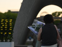 A woman offers a bouquet of flowers in front of the Cenotaph for the A-bomb Victims at Hiroshima Peace Memorial Park on the morning of Aug. 6, 2021. (Mainichi/Naohiro Yamada)
