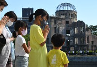 Children facing the hypocenter of the Hiroshima atomic bombing offer a prayer at the stroke of 8:15 a.m., the time the U.S. military dropped the atomic bomb on the city on Aug. 6, 1945, in this photo taken in Hiroshima's Naka Ward on the morning of Aug. 6, 2021. (Mainichi/Naohiro Yamada)