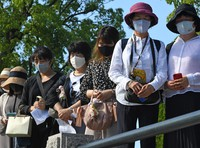 People offer a prayer at the stroke of 8:15 a.m., the time the U.S. military dropped the atomic bomb on the city on Aug. 6, 1945, in this photo taken in Hiroshima's Naka Ward on the morning of Aug. 6, 2021. (Mainichi/Naohiro Yamada)