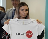 """Belarusian Olympic sprinter Krystsina Tsimanouskaya, who came to Poland Wednesday fearing reprisals at home after criticizing her coaches at the Tokyo Games, is showing an Olympic-related T-shirt with her slogan """"I Just Want to Run"""" after her news conference in Warsaw, Poland, on Aug. 5, 2021. (AP Photo/Czarek Sokolowski)"""
