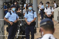 Police officers stand guard outside a court on July 30, 2021, in Hong Kong, as a pro-democracy demonstrator Tong Ying-kit exits the court after his sentencing for the violation of a security law during a 2020 protest. (AP Photo/Vincent Yu)