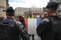 An anti-heath pass demonstrator holds a French flag as he faces police officers outside the Constitutional Council in Paris, on Aug. 5,2021. (AP Photo/Michel Euler)
