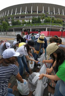 People are seen with garbage they collected near the National Stadium in Tokyo's Shibuya Ward on Aug. 9, 2021, a day after the Tokyo Olympics' closing ceremony. (Mainichi/Koichiro Tezuka)
