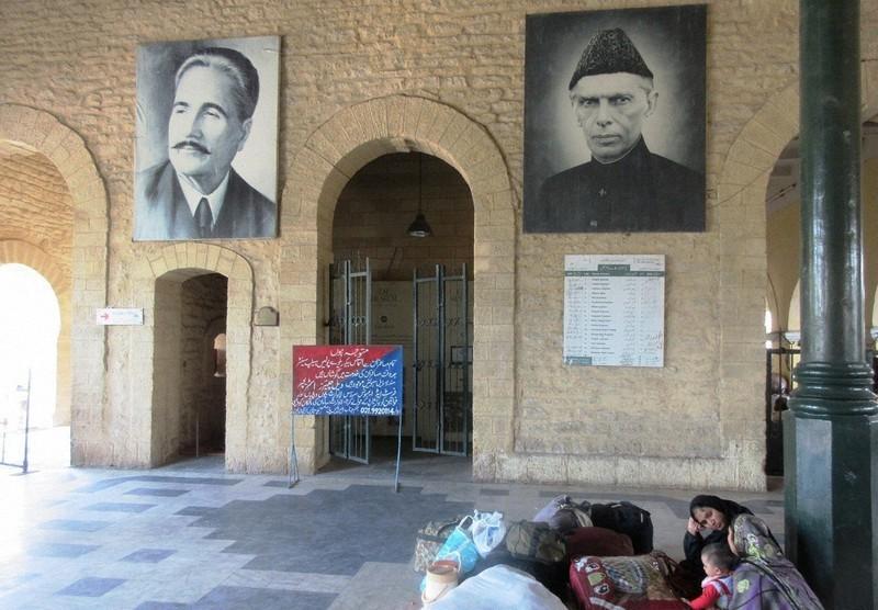 カラチの鉄道駅に掲げられたパキスタン建国の父ジンナーの肖像=右側(写真は筆者撮影)