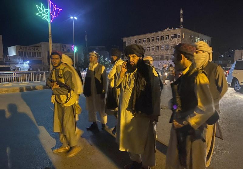 ガニ大統領の出国を受け、大統領府を掌握したタリバン戦闘員=2021年8月15日、AP