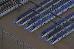 2019年の台風19号の影響で浸水した車両基地に並ぶ北陸新幹線の車両=長野市赤沼で2019年10月13日、本社ヘリから
