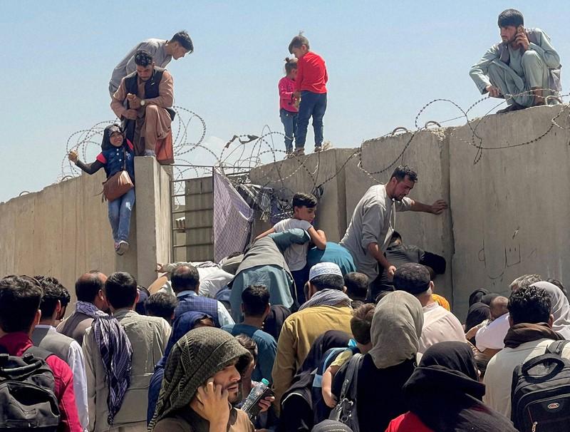 Orang-orang berusaha melewati tembok untuk memasuki halaman Bandara Internasional Kabul.  Sosok pria menarik seorang gadis juga ada di Kabul, 16 Agustus 2021, Reuters