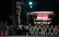 The front entrance of the Japan National Stadium is seen barricaded off ahead of the opening ceremony of the Summer Paralympic Games, in Tokyo's Shinjuku Ward on Aug. 24, 2021, as people raise a sign protesting against the event. (Mainichi/Yuki Miyatake)