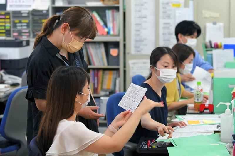 新型コロナウイルスの陽性者に電話連絡しながら、対応について話し合う保健師や看護師ら=東京都港区のみなと保健所で2021年8月5日午前10時24分、手塚耕一郎撮影(画像の一部を加工しています)