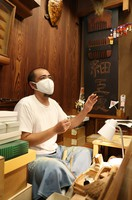 Yutaka Saito, head of traditional boxwood comb shop Yonoya Kushiho, is seen in a workspace of the shop in Tokyo's Taito Ward, with an old sign containing comb designs and the words,