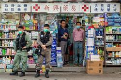 薬局前でマスク装着で警備にあたる香港の警察官 Bloomberg