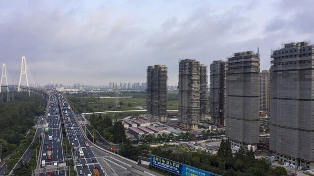 中国・上海の高速道路と建設中の高層マンション (Bloomberg)