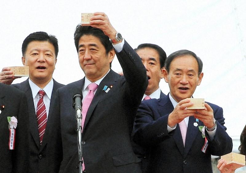 2013年当時、安倍晋三首相主催の「桜を見る会」で、乾杯する安倍首相(左から2人目)と菅義偉官房長官(右)=東京都新宿区の新宿御苑で2013年4月20日(代表撮影)