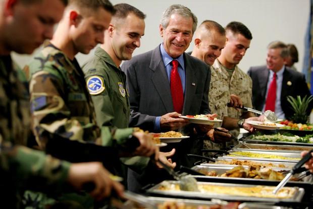 チャールストン空軍基地を訪問し、軍関係者と談笑するブッシュ元大統領 Bloomberg