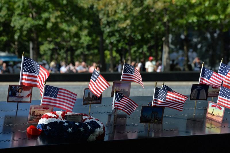 世界貿易センター(WTC)跡地の慰霊モニュメントの碑に立てられた星条旗=米ニューヨークで2021年9月10日、隅俊之撮影