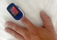 The pulse oximeter used to test blood oxygen saturation levels is seen on the finger of a man who was infected with the coronavirus despite being fully vaccinated, in this image provided by the man. The results of the test, taken at recovery accommodation, were within normal levels.