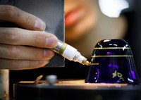 An artisan draws lines, markers for cutting patterns into the glass, during the