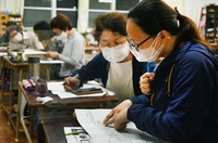 """A woman from the Philippines, foreground, practices writing kanji at the independent night school """"Yomikaki Kyoshitsu"""" in Fukuoka's Hakata Ward in this photo taken on April 28, 2021. The school has been forced to close several times due to the spread of the coronavirus. (Mainichi/Akihiko Tsuchida)"""