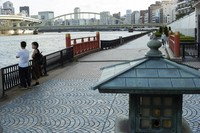 A man and a woman wearing face masks watch the Sumida River as they visit its riverside walking trail in Tokyo, on Sept. 16, 2021. (AP Photo/Hiro Komae)