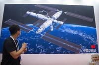 A visitor looks at a mural showing an artist's rendering of China's space station at the World Robot Conference in Beijing, on Sept. 11, 2021. (AP Photo/Mark Schiefelbein)