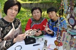魚の皮などで作った伝統工芸品を手にするニブフの女性たち=サハリン州立郷土博物館で2015年9月、真野森作撮影
