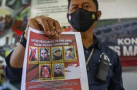 A police officer shows a wanted poster displaying the photos of two militants Ali Kalora, top left, and Jaka Ramadan, bottom left, who were killed during shootout with security forces, during a press conference at the Parigi Moutong Police Station in Parigi Moutong district, Central Sulawesi, Indonesia, Sunday, Sept. 19, 2021. (AP Photo/Mohammad Taufan)