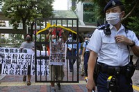 A police officer guard at a street during a protest against an election committee that will vote for the city's leader in Hong Kong Sunday, Sept. 19, 2021. (AP Photo/Vincent Yu)