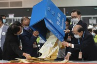 Erick Tsang, second left, Secretary for Constitutional and Mainland Affairs Bureau, helps officials pour out ballots from a box at a counting center in Hong Kong, on Sept. 19, 2021. (AP Photo/Vincent Yu)