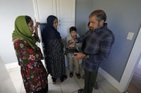 Abdul, right, who worked as a mechanic before he left Kabul, Afghanistan with his family about a month ago, shows his family a donated tea kettle as they stand in the kitchen of a rental house, on Sept. 16, 2021, that has been provided as a place for them to stay in Seattle. (AP Photo/Ted S. Warren)